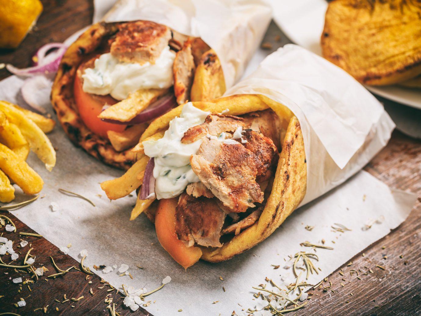 Greek gyros wraped in a pita bread on a wooden background