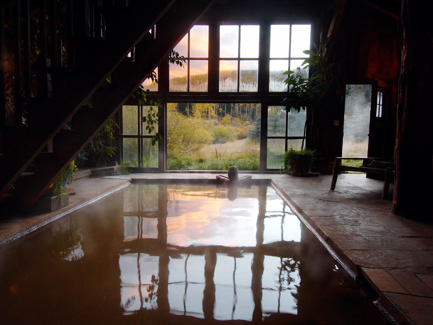woman soaking in pool in bathhouse interior