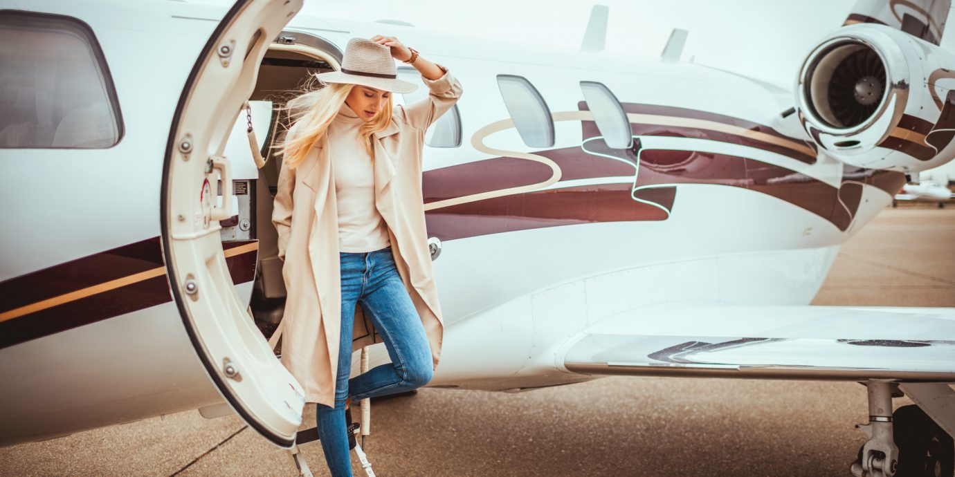 how to look stylish at the airport. Stylish woman watching her step as she's disembarking from a private airplane parked on an airport taxiway.