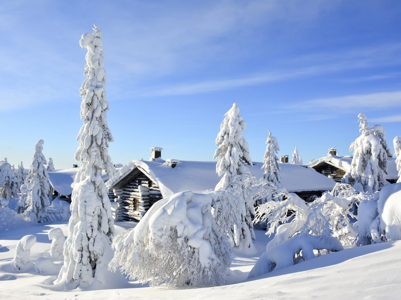 Cottages on snowy mountain on a sunny cold winter day on tourist resort in Lapland Finland.