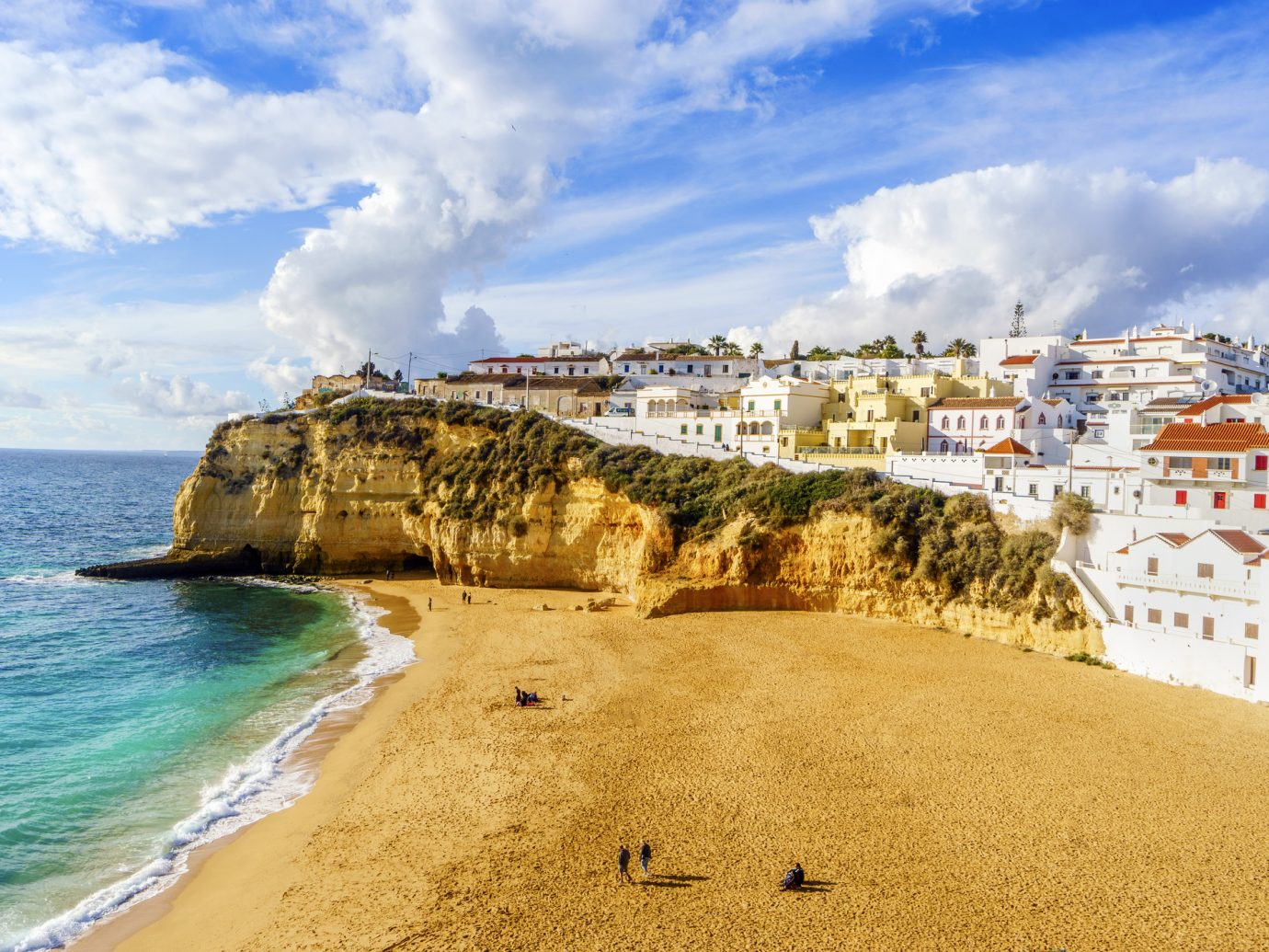 Wide sandy beach between cliffs and in front of charming white architecture in Carvoeiro, Algarve, Portugal