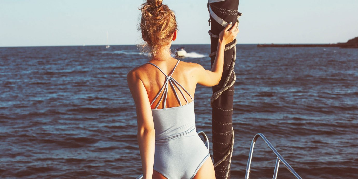 woman on a boat at sunset in a one-piece swimsuit