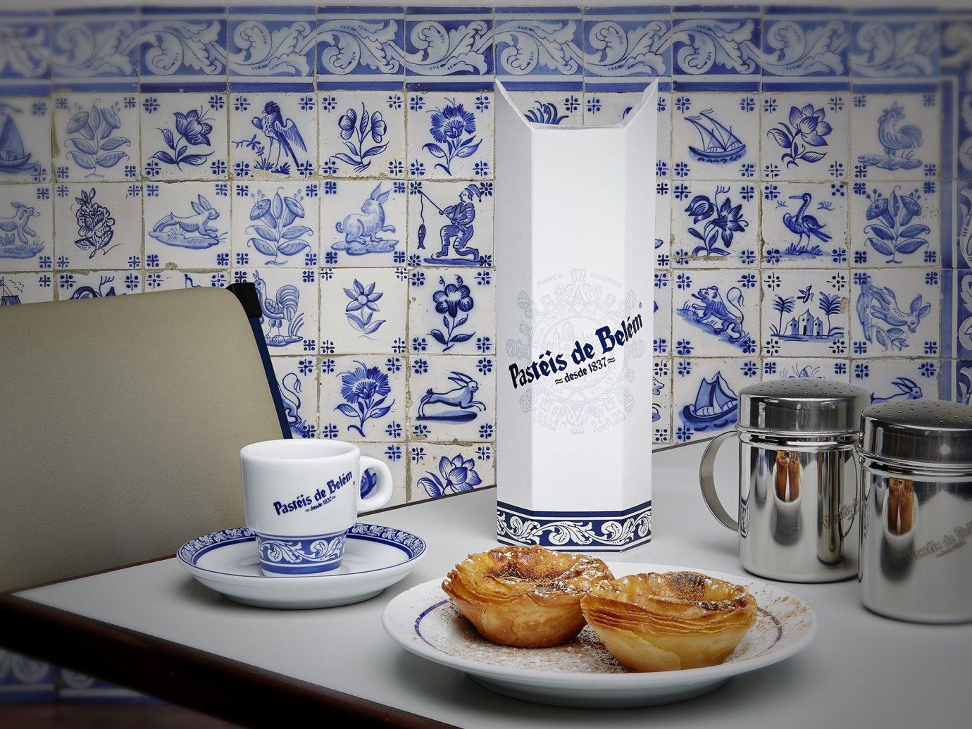 Pastel de Nata on a table at Antiga Confeitaria de Belém, Portuguese blue tiles in the background