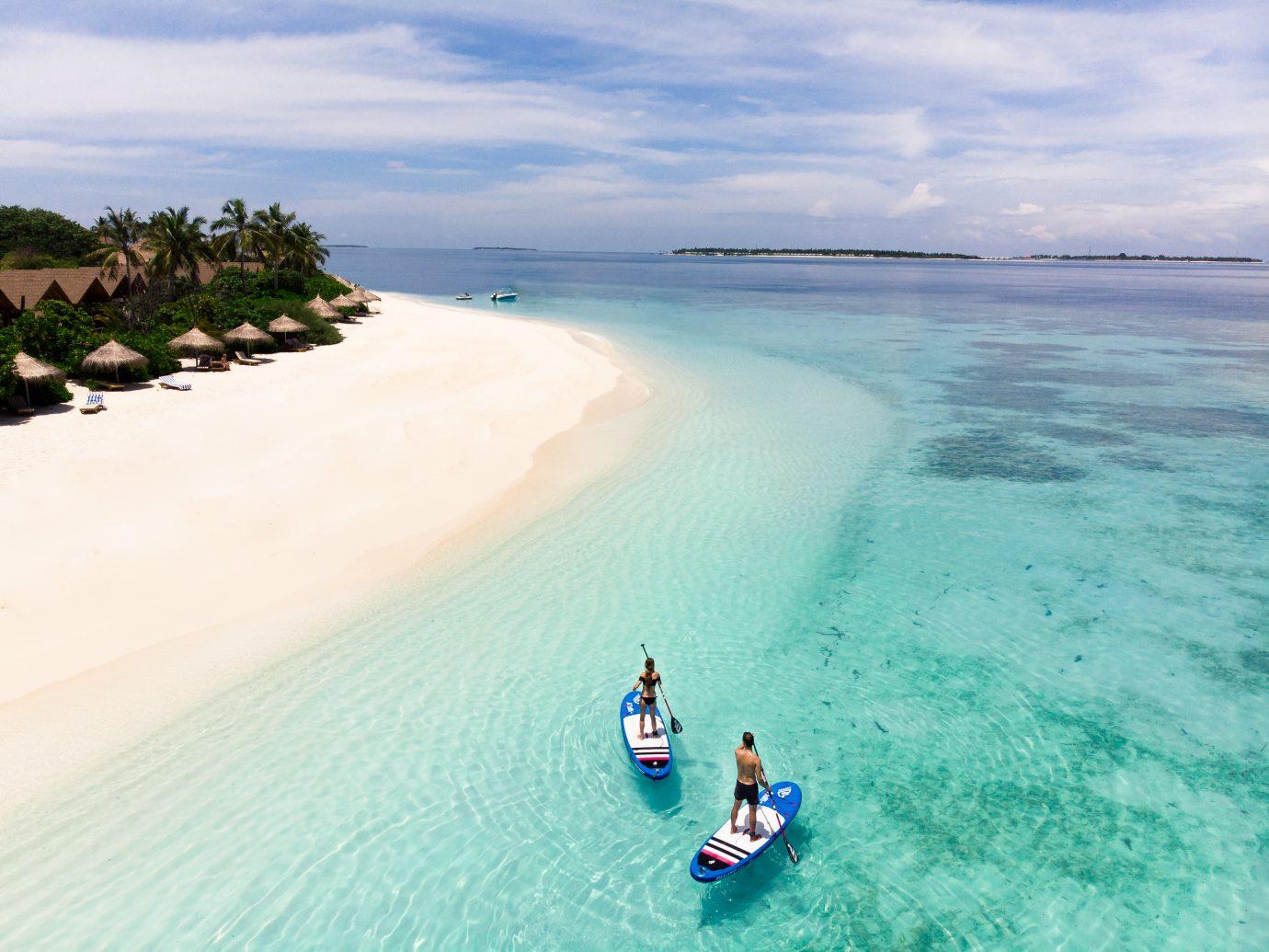 paddle boarders in the water at Reethi Faru Resort, Raa Atoll, Maldives