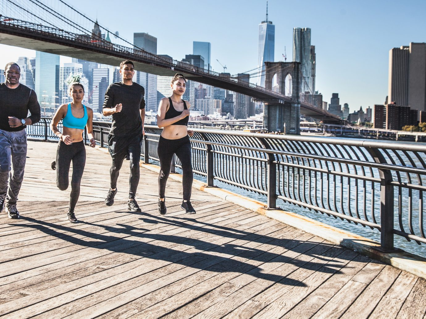 Group of healthy mixed race people running in DUMBO - New York City - USA. They are running in the city streets wearing professional sport clothes.