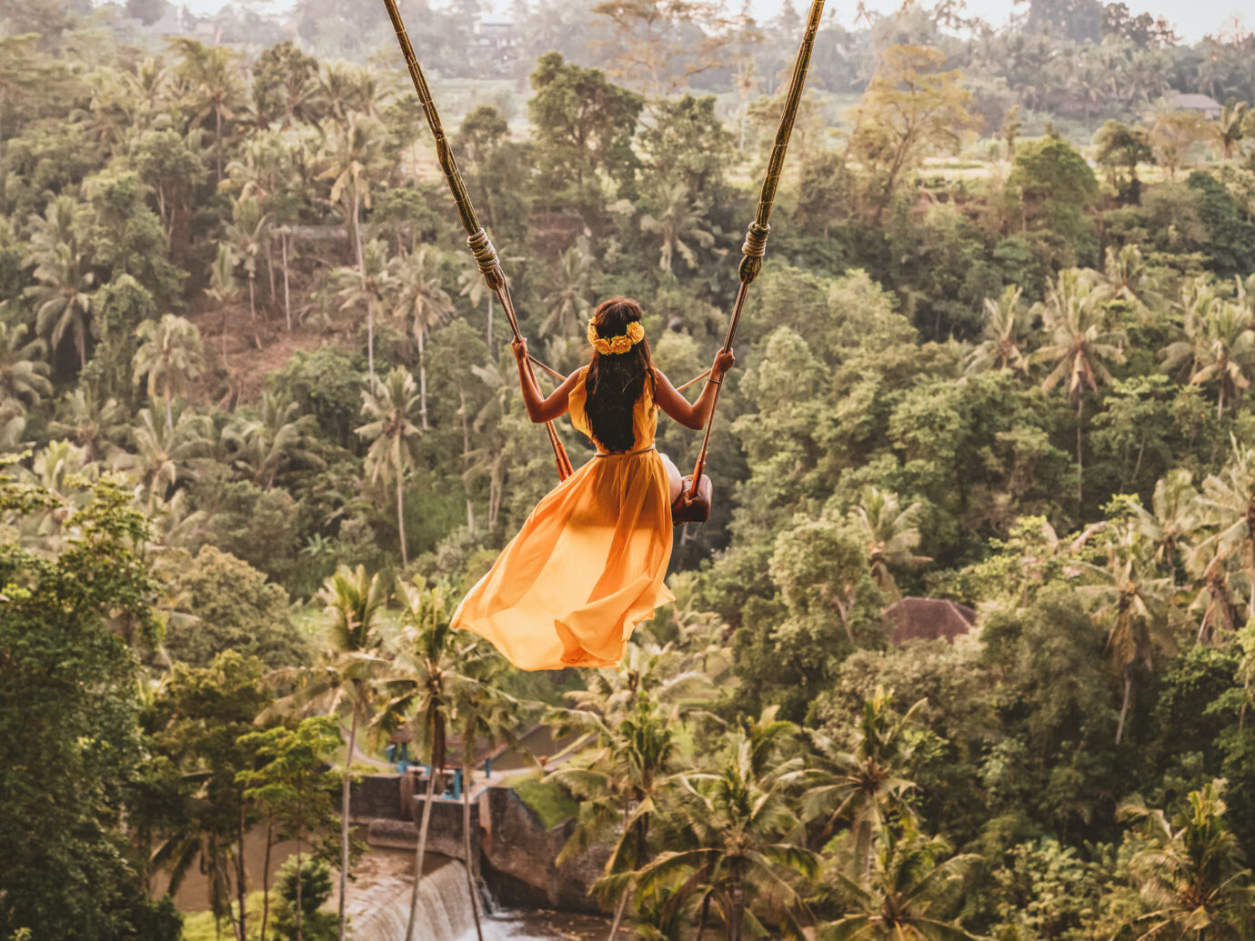 Photo of woman with long swing and forest view. Young woman swinging in the jungle rainforest of Bali island, Indonesia