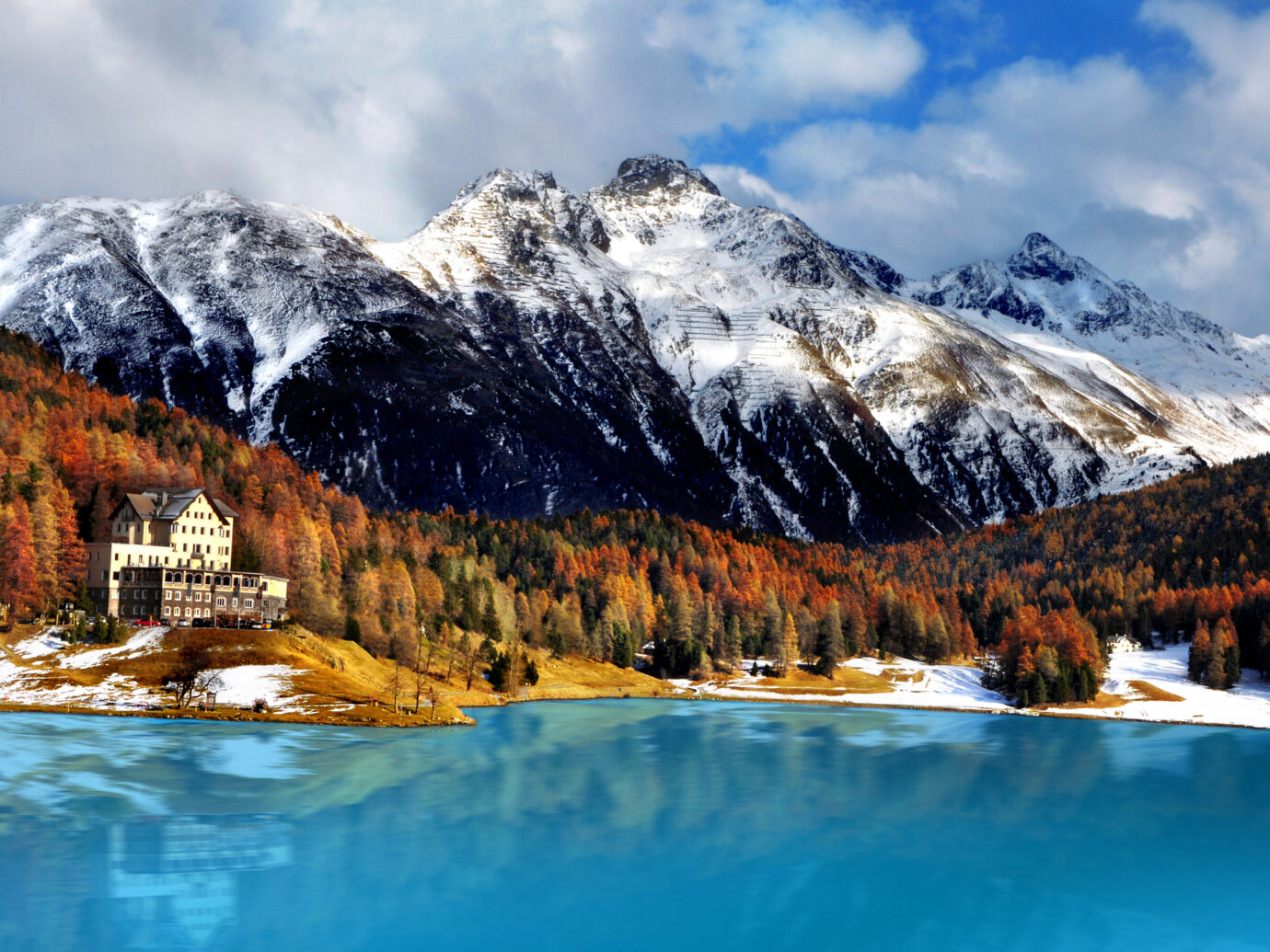 Idyllic lake surrounded by colorful trees in the Swiss Alps. St. Moritz.