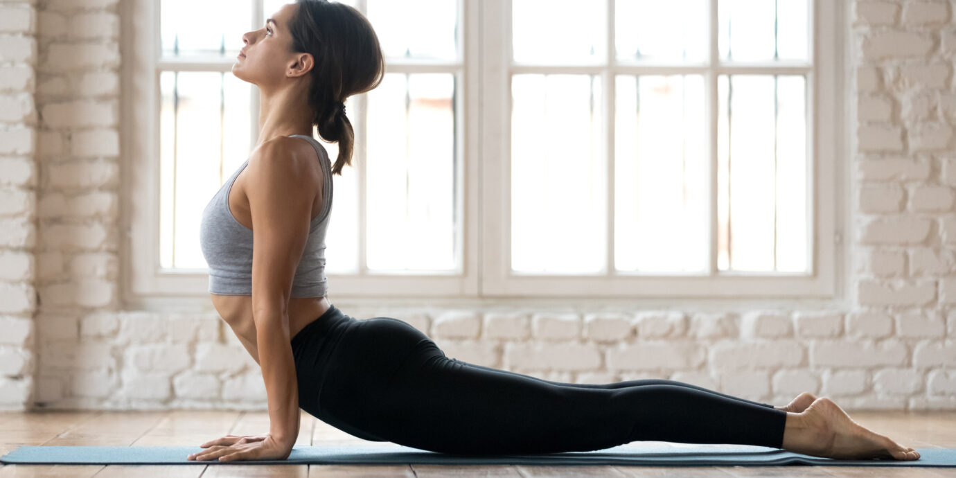 Young sporty woman practicing yoga, doing upward facing dog exercise, Urdhva mukha shvanasana pose, working out, wearing sportswear, pants and top, indoor full length, white yoga studio