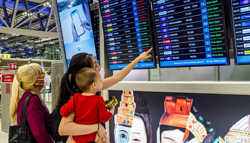 passenegers check departure times for flight at airport wearing coronavirus face masks