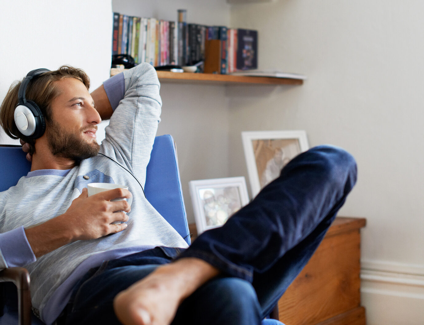 Shot of a young man having coffee while listening to music at home.