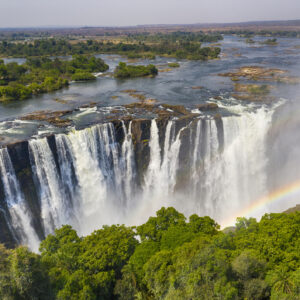 Aerial few of the world famous Victoria Falls with a large rainbow over the falls. This is right at the border between Zambia and Zimbabwe in Southern Africa. The mighty Victoria Falls at Zambezi river are one of the most visited touristic places in Africa.